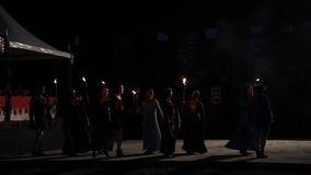 People in medieval clothes walk simultaneously in various patterns on stage stock video