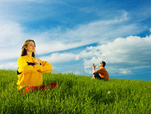 People Meditating in Field. Two people sitting in an open field of green grass on a bright sunny day, meditating