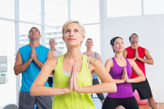 People meditating in fitness club Stock Photo