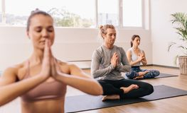 People meditating in yoga class. People meditating while sitting in room. Young men practicing yoga in gym class with people sitting around stock images