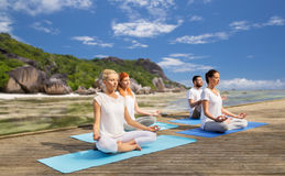 People meditating in yoga lotus pose outdoors Royalty Free Stock Photo