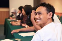 People at meeting. Portrait of young man at meeting stock photography