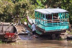 People of Mekong Delta, Cai Be, Vietnam. Mekong Delta, Vietnam-December 10, 2013. Local Vietnamese man paint a boat on December 10, 2013 at Mekong Delta, Cai Be Stock Images
