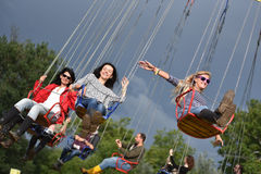 People in merry go round, swing ride, highland spinner Stock Photography