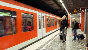 People at the metro subway station. Hamburg, Germany - October, 10, 2016: People at subway metro underground tube station walk to get the arriving train Stock Photography