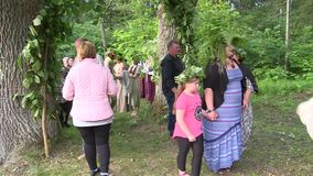 People at midsummer holiday. STIRNIAI, LITHUANIA - JUNE 23, 2018: People gather together to celebrate annual Midsummer holiday day. People go through arch stock video