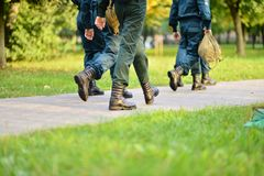 People in military uniform walking on road. Cropped image of people in military uniform walking on road royalty free stock image