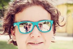 People are mirroring in sunglasses of teenage boy stock image