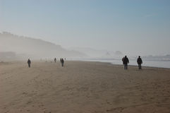 People on misty ocean beach. Visitors at Cannon Beach, Oregon, stroll along the sandy coastline in the mist and sun Royalty Free Stock Photos