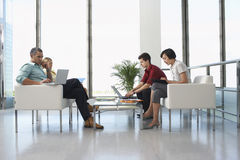 People At Modern Waiting Room In Office. Full length side view of four business people sitting in modern waiting room at office Royalty Free Stock Photography