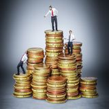 People on money. Business people standing on a stack of gold colored coins business cost concept stock images