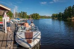 People on a moored motorboat at a boat refueling station with sailboats. JARFALLA, SWEDEN - JUNE 9, 2018: Seascape front view of people on a moored motorboat at stock photos