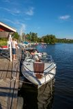 People on a moored motorboat at a boat refueling station with sailboats. JARFALLA, SWEDEN - JUNE 9, 2018: Vertical seascape front view of people on a moored royalty free stock photo