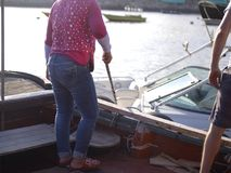 People Mooring Boats. People mooring a boat and marina, outdoor contra light shot with shallow depth of field Stock Photo