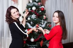 People, motherhood, family, christmas and adoption concept - happy mother and daughter hugging at home royalty free stock image