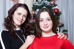 People, motherhood, family, christmas and adoption concept - happy mother and daughter hugging at home stock photography