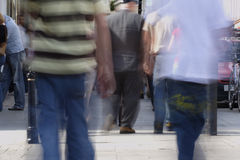 People in motion. Crowd of people on the high street, motion blurred to show movement royalty free stock photo