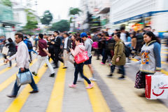 People in motion blur crossing a street in Hong Kong Stock Images