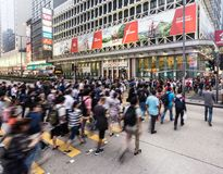 People in motion in Hong Kong. HONG KONG - APRIL 26, 2017: People, captured with blurred motion, cross Nathan road in the very crowded Mong Kok shopping district Stock Photos