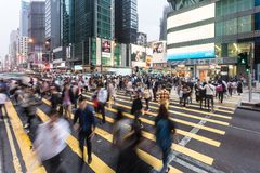 People in motion in Hong Kong. HONG KONG - APRIL 26, 2017: People, captured with blurred motion, cross Nathan road in the very crowded Mong Kok shopping district Royalty Free Stock Photo