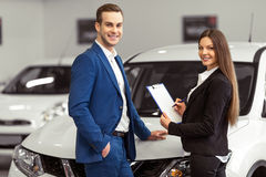 People in motor show. Beautiful young women in classic suit and handsome young men are smiling and looking at camera while examining a car in a motor show Royalty Free Stock Images