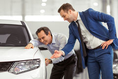 People in motor show. Handsome young men in classic blue suit is smiling while showing a car to middle aged customer in a motor show Royalty Free Stock Photography