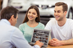 People in motor show. Young couple is smiling while buying a car. Handsome middle aged worker of motor show is showing cars using a laptop Stock Photos