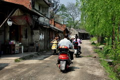 Pengzhou, China: Motorbikes on Old Street. People on motorbikes ride along a dirt road lined with weeping willow trees past a row of old one and two story houses royalty free stock images