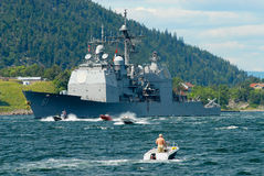 People in motorboats follow norwegian military ship in a fjord in Frogn, Norway. Stock Images
