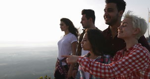 People on mountain top enjoying landscape, friends group tourists, girl point finger. Slow Motion 60 stock video footage