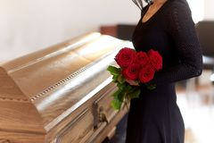 Woman with red roses and coffin at funeral Royalty Free Stock Image