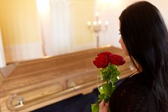 Woman with red roses and coffin at funeral Stock Photos