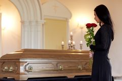 Woman with red roses and coffin at funeral Stock Photography