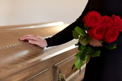 Woman with red roses and coffin at funeral stock images