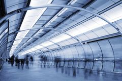People on the move. People walking in a futuristic tunnel. Shot with slow shutter speed to create blur effect Royalty Free Stock Photo