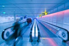 People moving in airport corridor stock photos