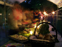 People Moving in Buffet Line. Candlelit tropical buffet table filled with delicious food. People are just visible as motion blur as they move through the line to Royalty Free Stock Photo