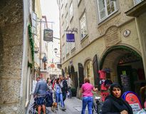 People moving through busy narrow street of historic buildings a. SALZBURG, AUSTRIA - SEPTEMBER 6 2017; People moving through busy narrow street of historic Stock Photo