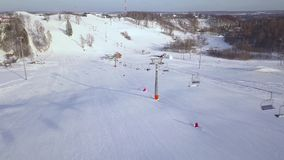 People on moving on chairlift on ski mountain at winter resort aerial view. Ski elevator for transportation skiers and. Snowboarders on snow mountain in ski stock video footage
