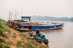 People Moving Commodities to The Land by Boat in The River at Luang Prabang, Laos.  royalty free stock photography