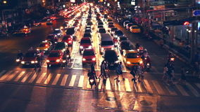 People moving at crossroad in crowded evening city street. Bangkok, Thailand stock video