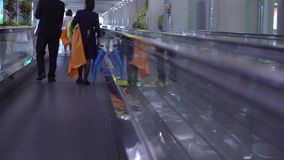 People moving on flat escalators in a airport terminal or train station. stock video