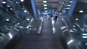 People moving on flat escalators in a airport terminal or train station. Slow motion.  stock footage