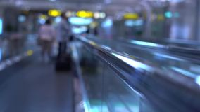 People moving on flat escalators in a airport terminal or train station. Slow motion stock video
