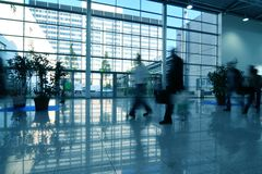 People moving in glass corridor Stock Images