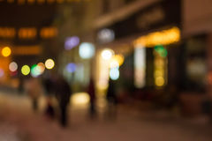 People moving on old city winter night street blurred. People moving on the old european city winter night street defocused blurred abstract image royalty free stock photography
