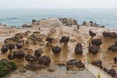 People and Mushroom rocks at the Yehliu Geopark Stock Photo