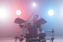 People, music and hobby concept - man plays with drumsticks on drums on the stage stock photos