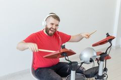 People, music and hobby concept - Man with white headphones playing the drums set over light background stock photos