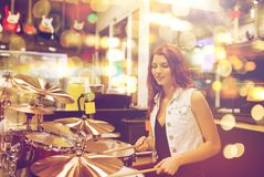 Female musician playing drum kit at music store. People, musical instruments and entertainment concept - smiling female musician playing drum kit at music store Stock Photos